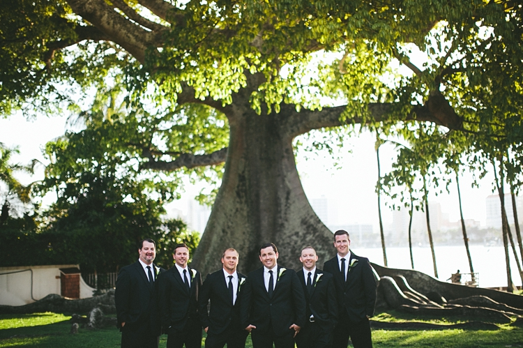 Groomsmen standing by giant tree at Royal Poinciana Chapel