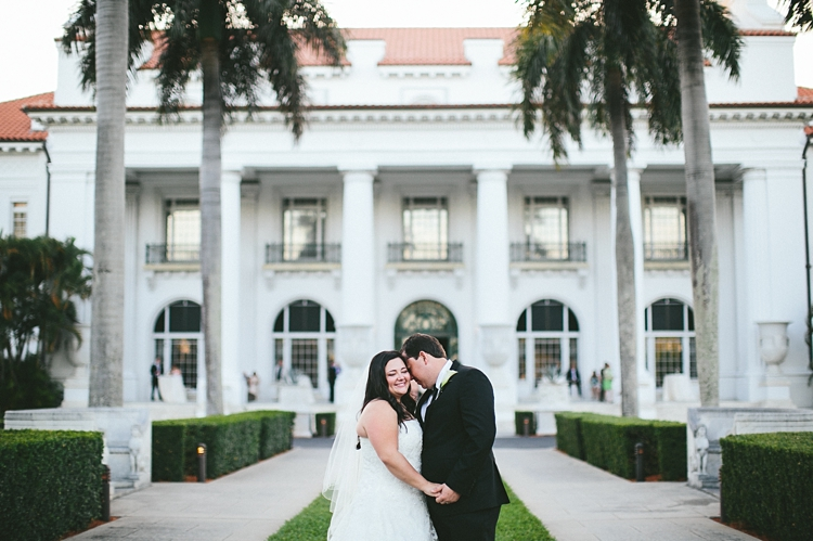 Bride and groom kiss in front of Flagler Museum