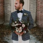 Groom in floral jacket holding flower bouquet