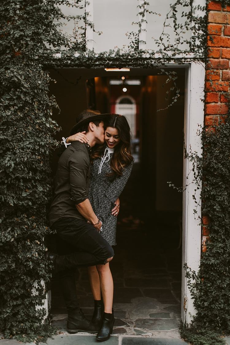 Engaged couple kissing in courtyard of New Orleans French Quarter