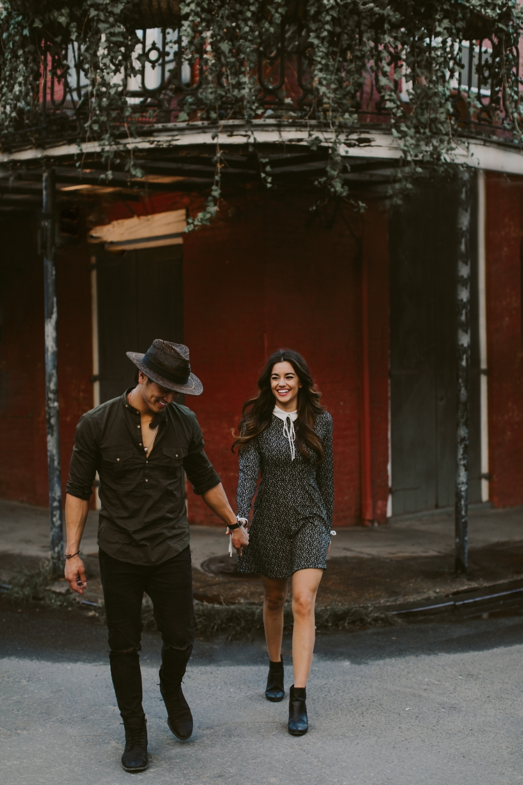 Engaged couple laughing in the streets of New Orleans crossing the street