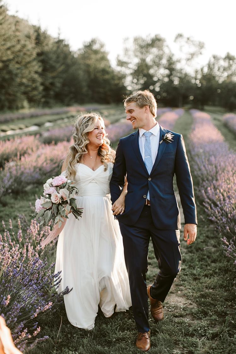 Couple walk through lavender field on their wedding day