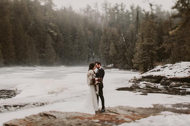 Bride wearing fur kisses her groom in the fog in Toronto